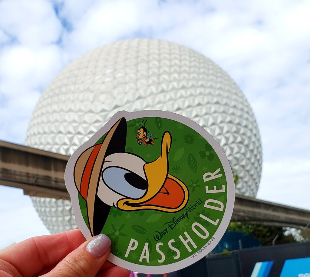 epcot ball with donald duck magnet being held in womans hand
