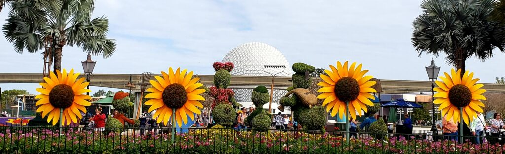 epcot ball with giant sunflowers and topiaries
