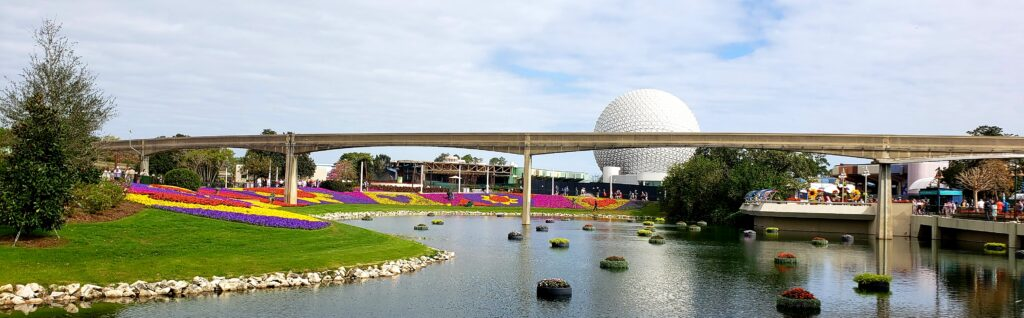 landscape picture of epcot ball and the monorail tracks in front with flowers