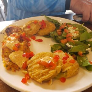 white plate fried green tomatoes and crab cakes garnished with salad