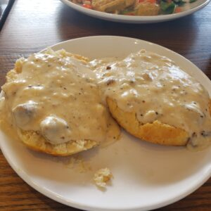 white plate with open biscuit and topped with sausage gravy