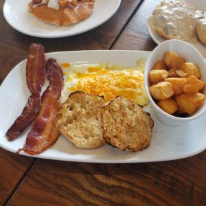 white plate 2 slices of bacon eggs with cheese english muffins and potatoes