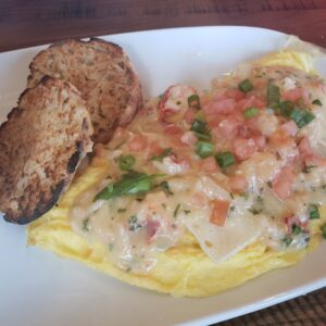 white plate with omlette topped with tomato and lobster english muffin on the side