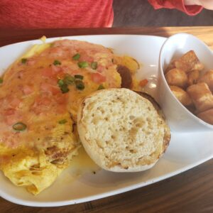 white plate with omelette english muffin and a side of potato