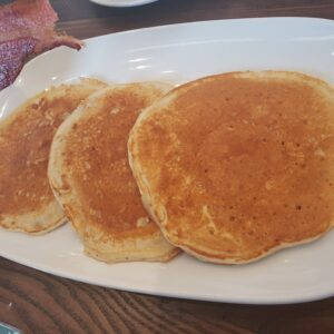 white plate with 3 plain pancakes and bacon on the side