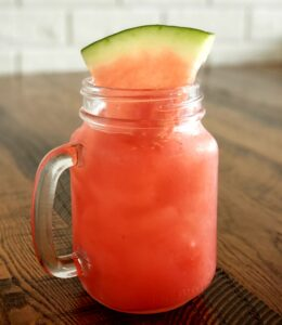 mason jar with handle filled with watermelon and cucumber juice and topped with a watermelon slice