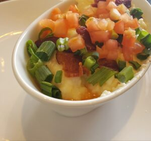 White bowl filled with grits topped with bacon, onions and tomatoes