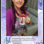 woman holing coffee cup with figment on it and a quote on art