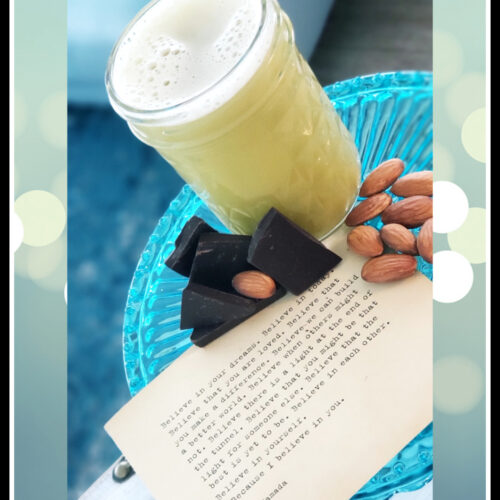 teal tray with celery juice in clear up chcoclate and nuts nest to the glass with quotes