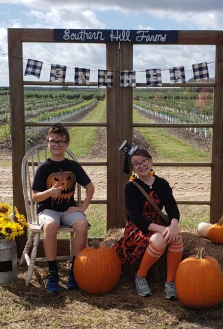 2 kids sitting with pumpkins and hay for a picture