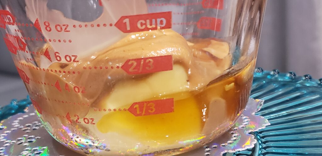 glass measuring cup with butter honey and peanut butter in it