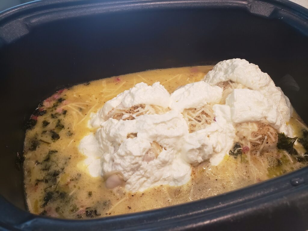 dressing in crockpot with cream cheese on top