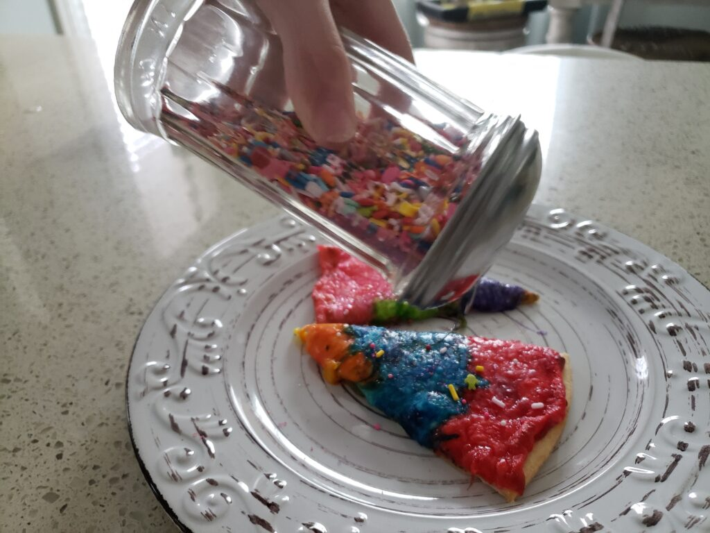 rainbow pizza - sliced with a person sprinkling sprinkles on it