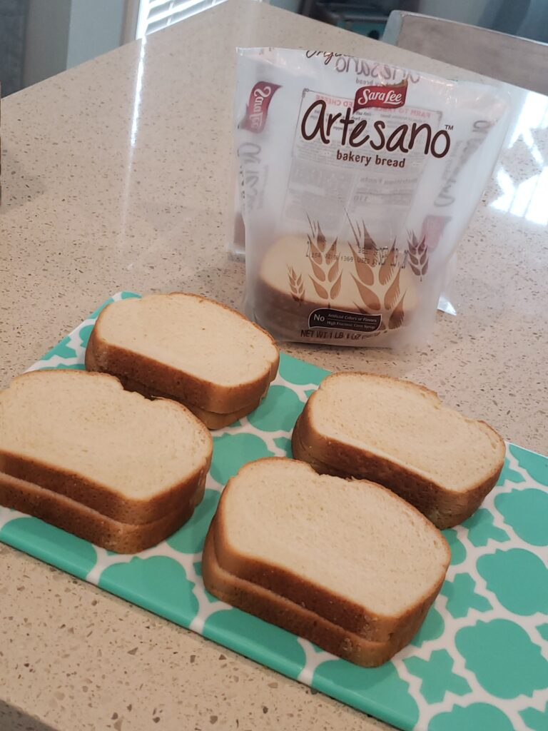 artesano bread package in front of a cutting board with 8 slices of bread