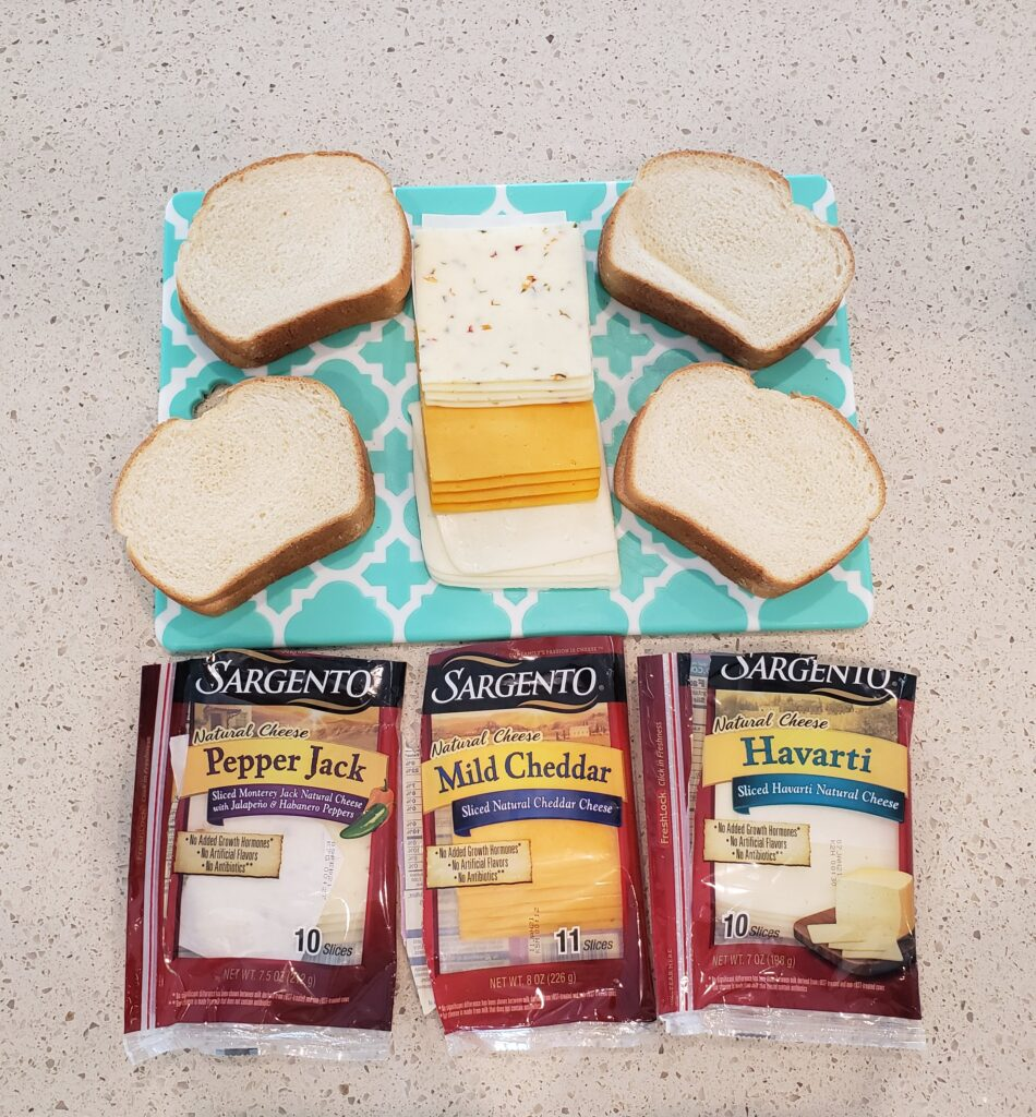4 slices of bread on a cutting board with cheese in the middle and the packages of cheese in front