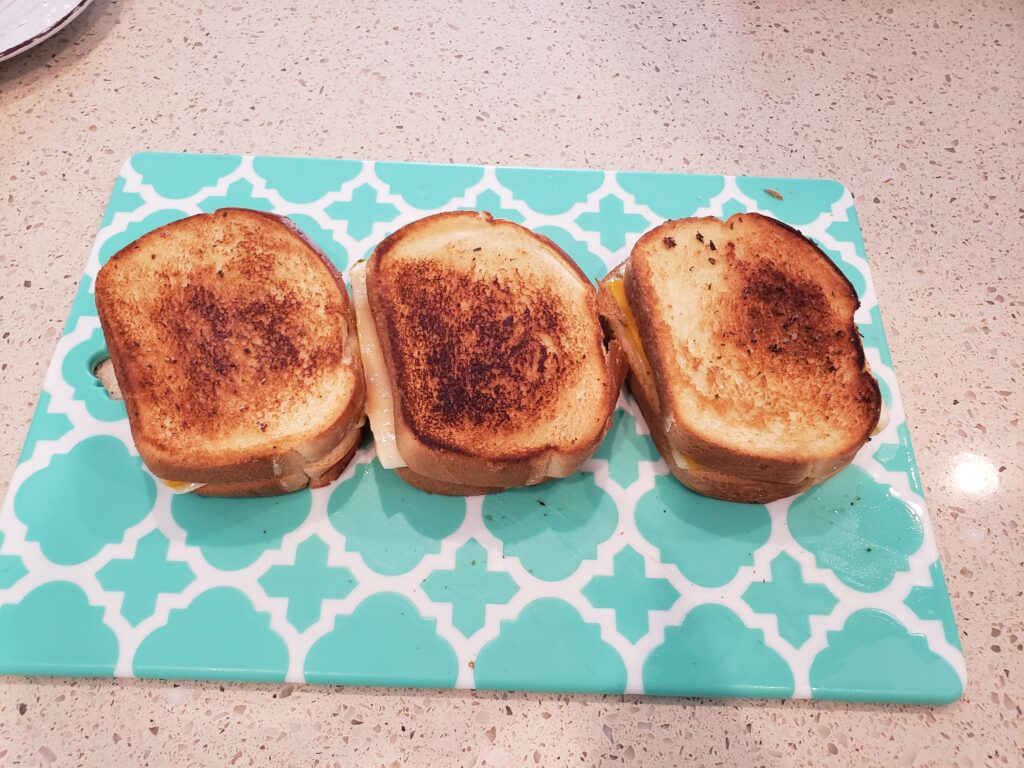 grilled cheese on a cutting board side by side 3 of them