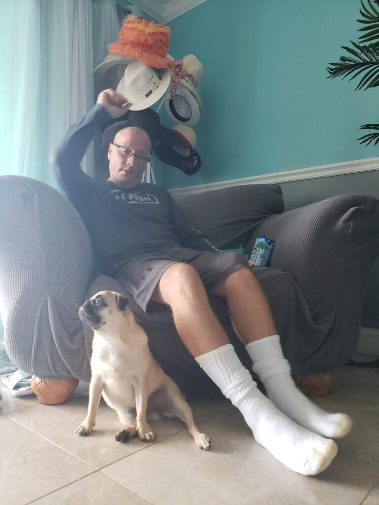 honey the pug in front of a man in a chair