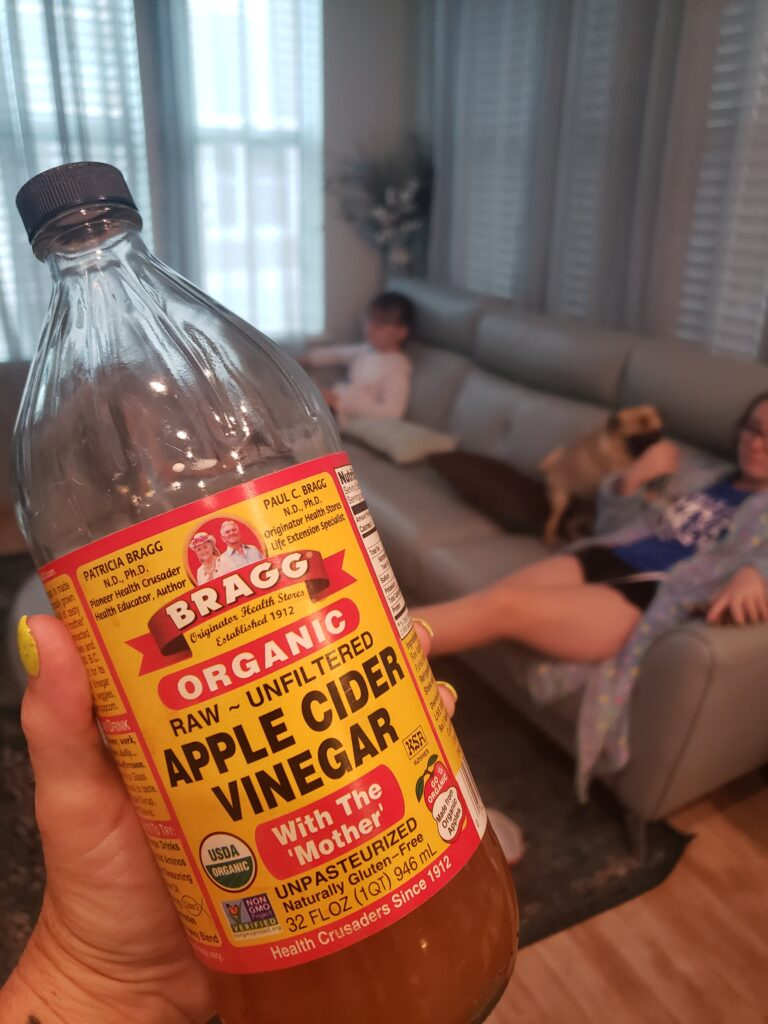 apple cider vinegar in a womans hand with the kids in the back ground