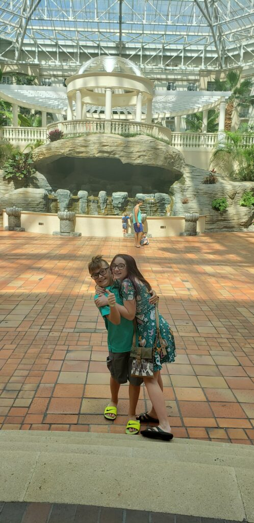 atrium area on the gayloard palms 2 kids hugging in front - glass ceiling