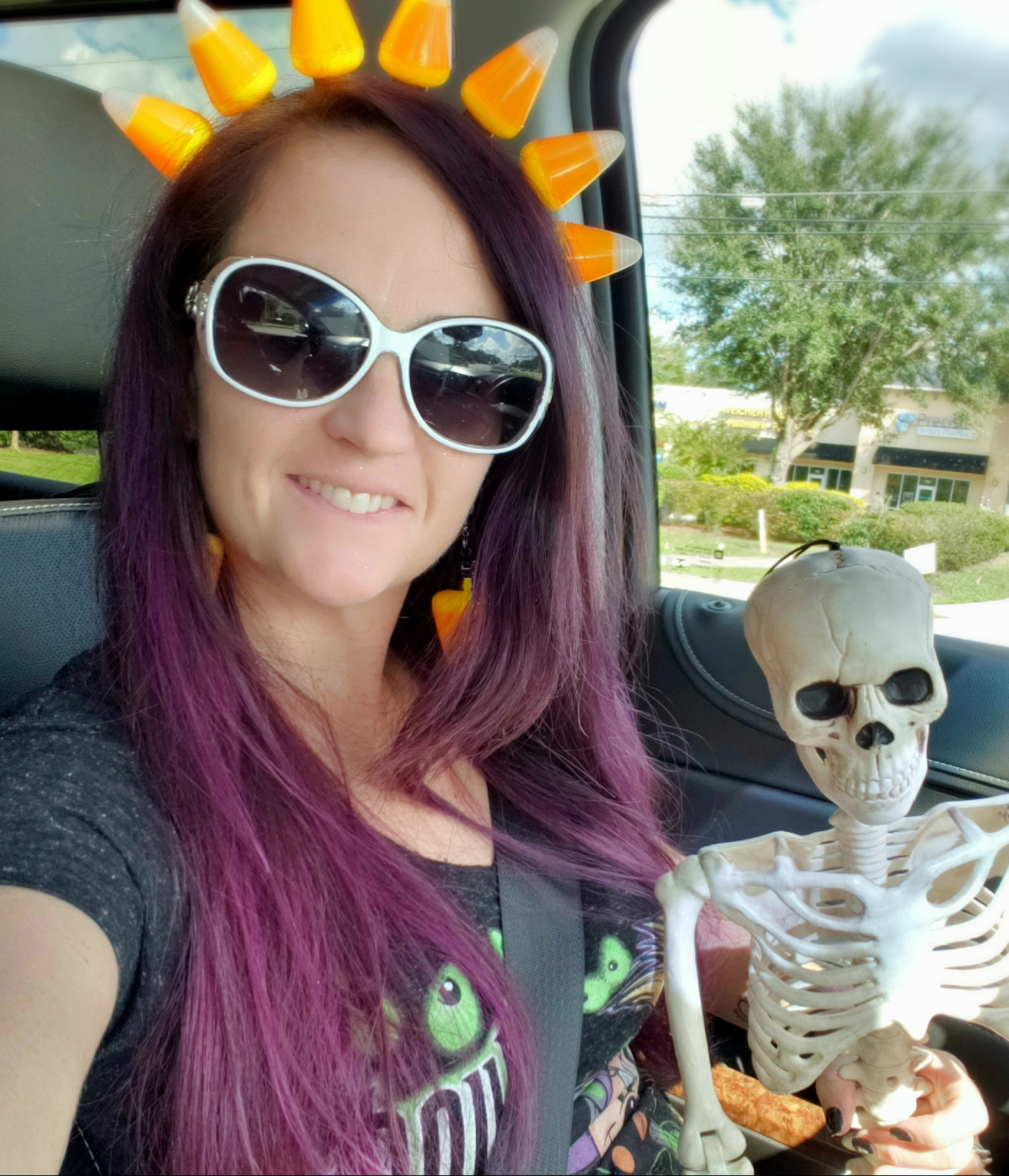 a woman in a car with a candy corn headband sitting with a skeleton