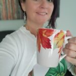 a woman smiling holding a cup with fall leaves on it