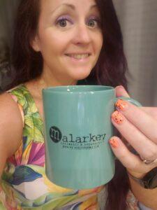 woman holding malarkey coffee cup