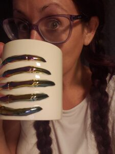 woman with glasses drinking from a skeleton hand