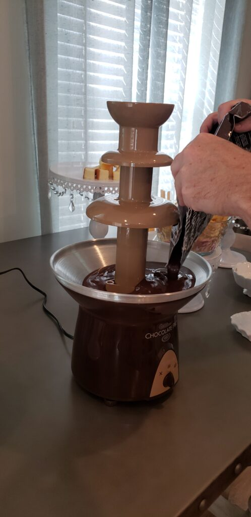 The Epic Chocolate Fountain on a table with man putting chocolate into the fountain