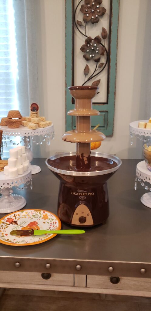 The Epic Chocolate Fountain on a table with chocolate dripping from it